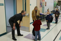Deputy Superintendent Denny Waters (left) and school counselor Chris Linquist (right) greet a kindergartner on the first day of school (image without graphic overlay)