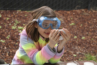 A 3rd grader wears protective goggles while studying a water sample