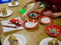 South Ridge Elementary kindergarteners and third graders work together to build gingerbread houses.  Here they use bowls of sticky icing to glue candies to houses.