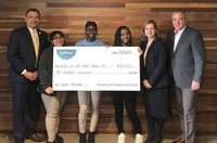 OnPoint President and CEO, Rob Stuart and Chief Talent Officer, Jackie Dunckley present a $100,000 donation to De La Salle North Catholic High School's President, Oscar Leong and three students completing their work-study program at OnPoint.